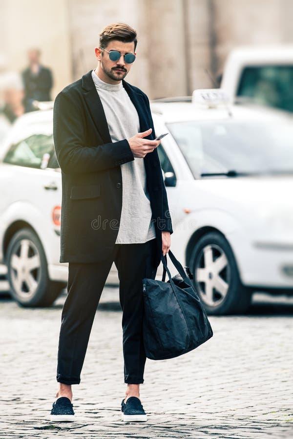 Modelo hermoso del hombre con las gafas de sol y el teléfono celular al aire libre fotografía de archivo