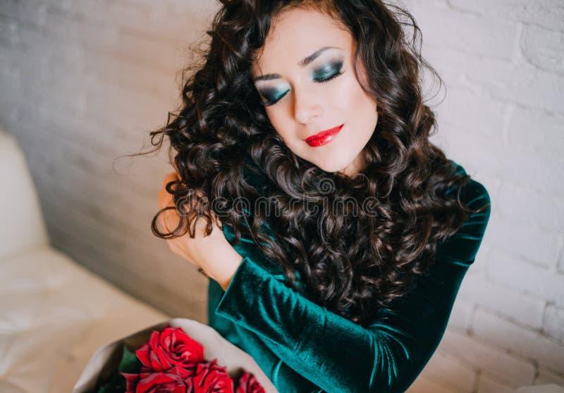 Modelo hermoso en el vestido esmeralda del terciopelo que se sienta en un sofá blanco imagen de archivo