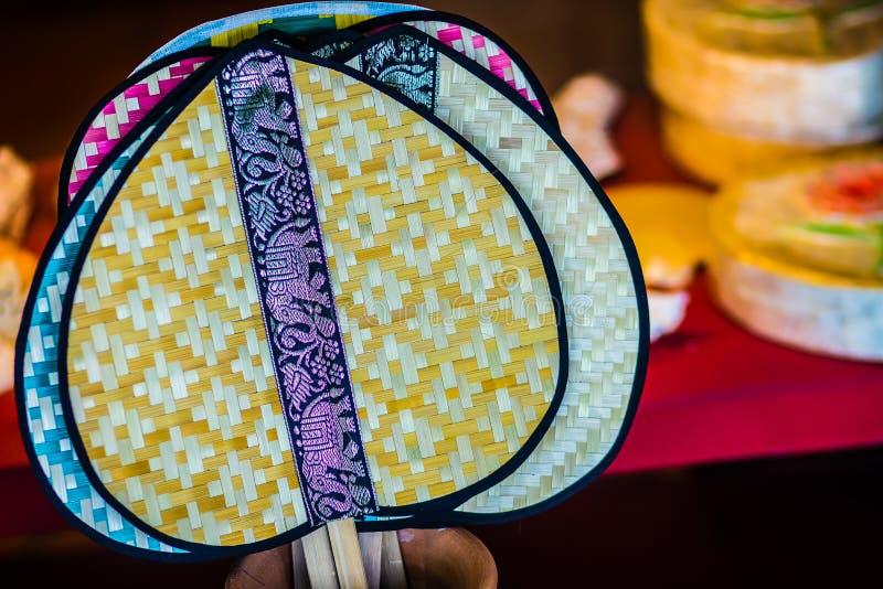 Modelo hermoso en la fan nativa tailandesa hecha del bambú para la venta en el mercado local fotos de archivo libres de regalías
