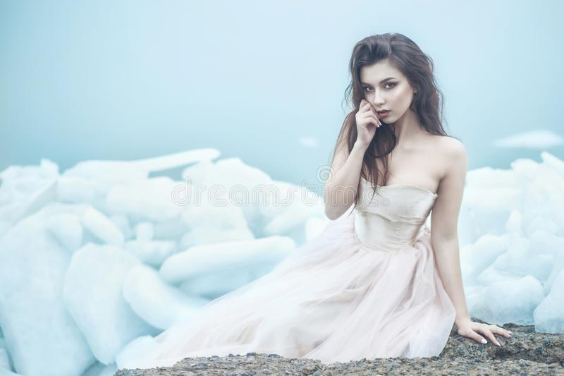 Modelo hermoso joven en el vestido de bola sin tirantes lujoso del corsé que se sienta en las losas del hielo quebrado en la play foto de archivo libre de regalías