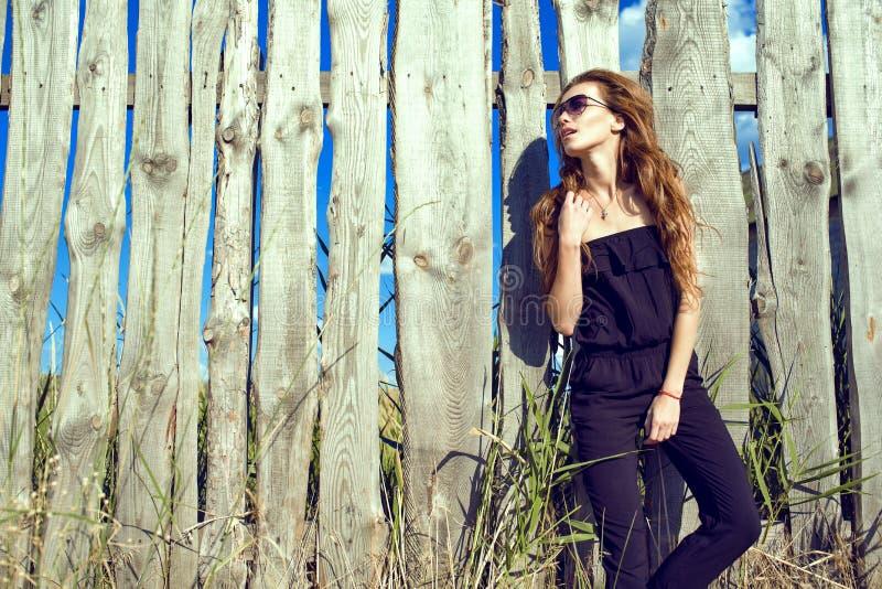 Modelo hermoso que lleva el mono sin tirantes negro y las gafas de sol de moda que se colocan en la cerca de madera lamentable vi imagen de archivo