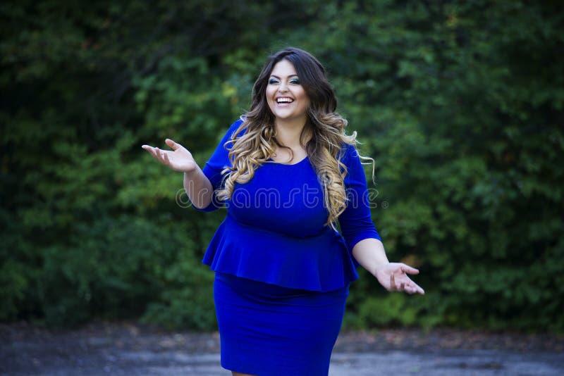 Modelo hermoso sonriente feliz joven del tamaño extra grande en vestido azul al aire libre, mujer del xxl en la naturaleza foto de archivo