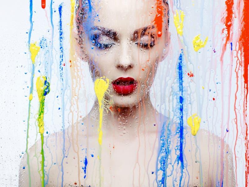 Modelo hermoso a través del vidrio con colores brillantes foto de archivo libre de regalías
