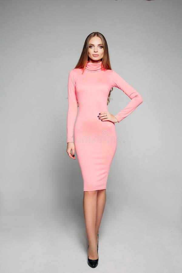 Modelo imponente elegante en vestido rosado de cuerpo-abrazo casual y talones imagen de archivo libre de regalías