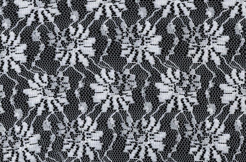 Modelo inconsútil del cordón blanco con las flores en fondo negro ilustración del vector