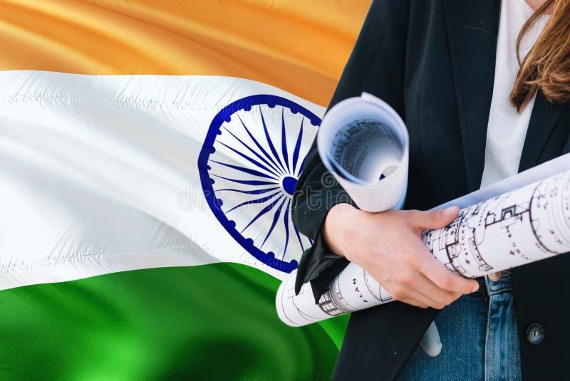 Modelo indiano da terra arrendada da mulher do arquiteto contra o fundo de ondulação da bandeira da Índia Conceito da constru??o  fotos de stock