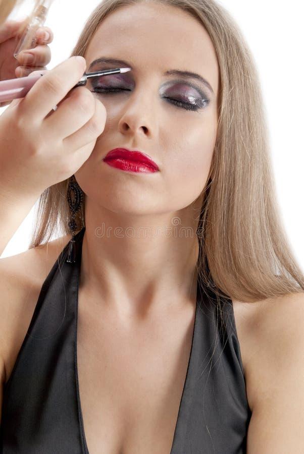 Modelo joven hermoso que consigue maquillaje de la manera imagen de archivo
