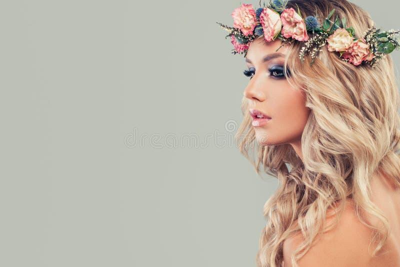 Modelo joven perfecto con las flores en el pelo principal y rizado fotografía de archivo libre de regalías