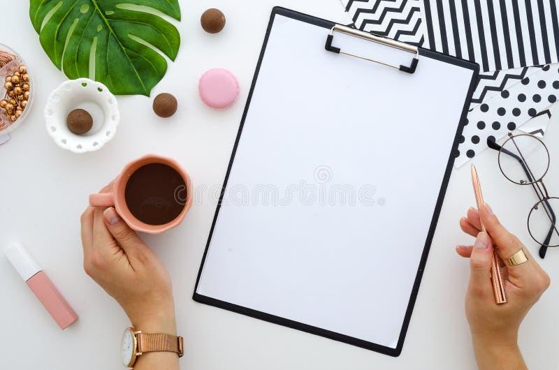 Modelo liso da prancheta da configuração O ` s da mulher entrega a posses a placa dourada do copo da pena e de café zombaria da f imagem de stock