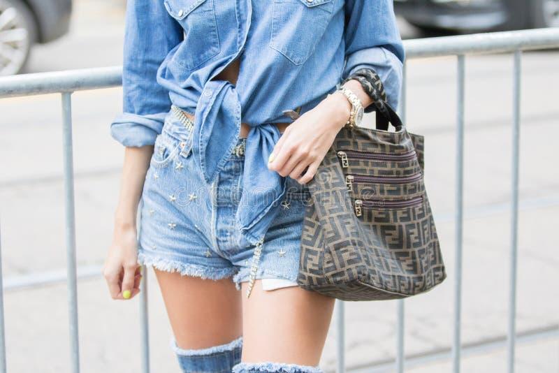 Modelo lleva pantalones cortos de denim, una camisa de denim y una bolsa Fendi imagenes de archivo