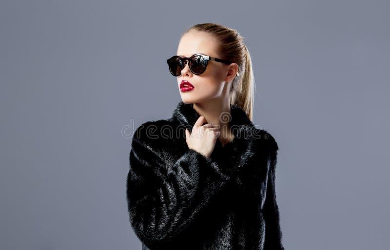 Modelo louro à moda nos óculos de sol e no casaco de pele preto imagem de stock