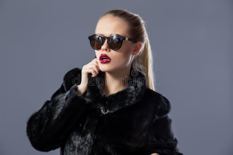 Modelo louro à moda nos óculos de sol e no casaco de pele preto fotografia de stock royalty free