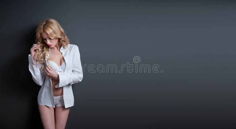 Modelo louro atrativo com o sutiã, a camisa branca e o short estando no fundo cinzento. Retrato da forma de uma menina loura bonit foto de stock