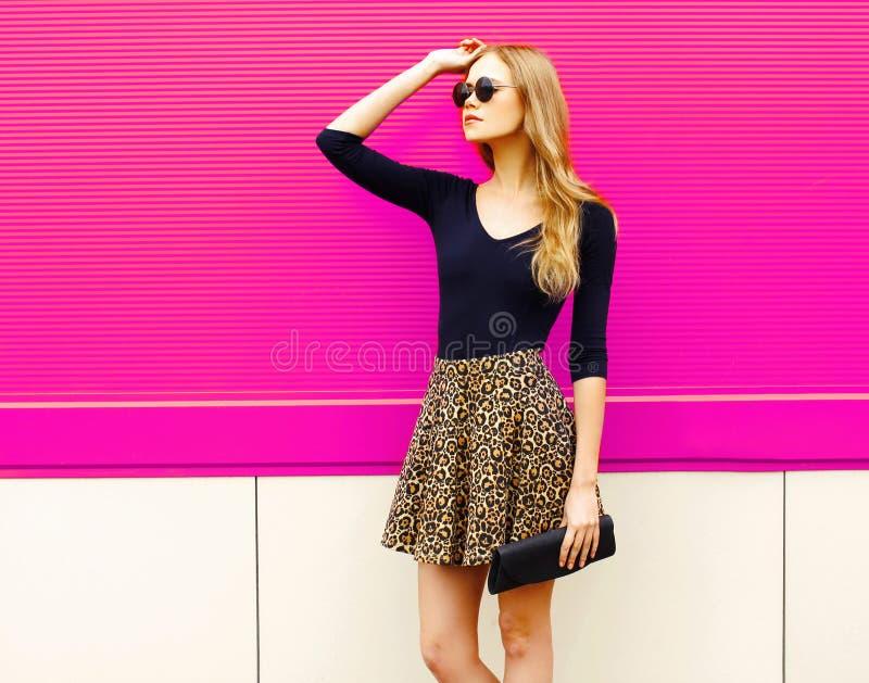 Modelo louro bonito da mulher do retrato que levanta na saia do leopardo, óculos de sol com embreagem da bolsa fotos de stock