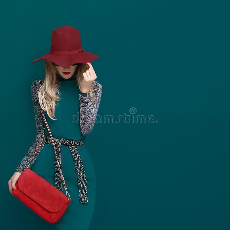 Modelo louro bonito no chapéu vermelho elegante e em uma embreagem vermelha na GR imagem de stock royalty free