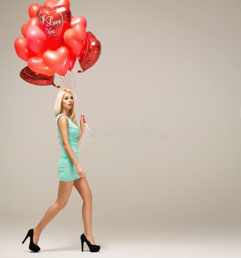 Modelo louro novo atrativo da mulher com os balões no isola do movimento fotografia de stock royalty free