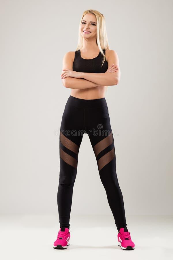 Modelo louro que veste leggins pretos e instrutores cor-de-rosa imagem de stock royalty free