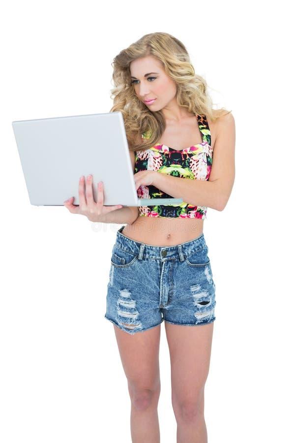 Modelo louro retro concentrado usando um portátil foto de stock
