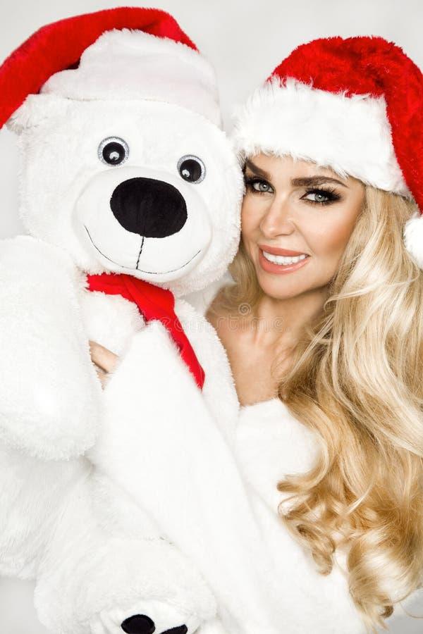 Modelo louro 'sexy', sorrindo bonito vestido em um chapéu de Santa Claus, guardando um urso de peluche Menina sensual da beleza p foto de stock