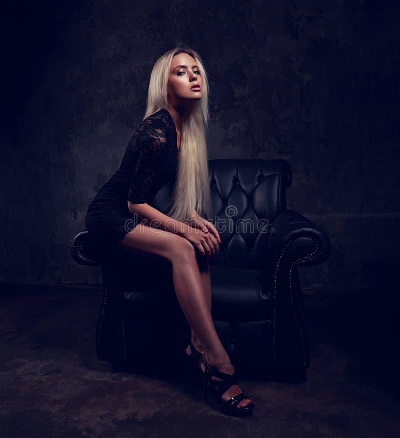 modelo magro do blod com pés longos nos saltos altos que sentam-se na poltrona da forma no vestido preto e que levantam em dramát foto de stock royalty free