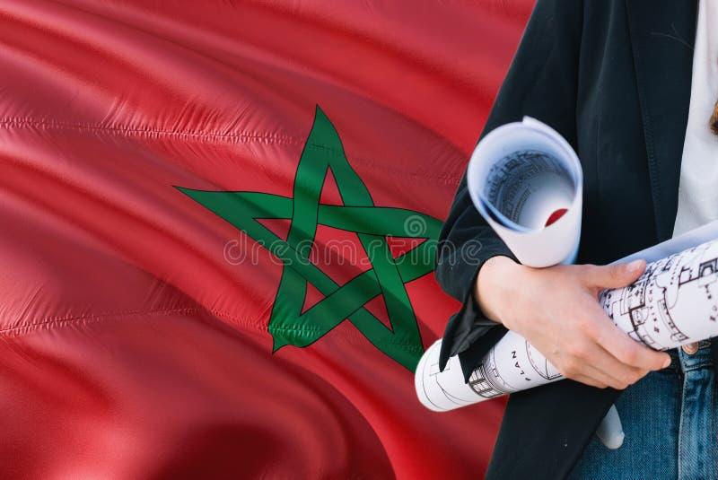 Modelo marroquí de la tenencia de la mujer del arquitecto contra fondo de la bandera de Marruecos que agita Concepto de la constr fotografía de archivo libre de regalías