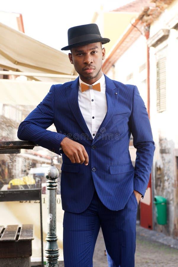 Modelo masculino afro-americano fresco que levanta na rua da cidade com terno e bowtie imagens de stock