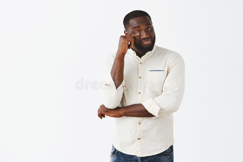 Modelo masculino afroamericano barbudo hermoso masculino en la camisa blanca que azota lágrima del ojo después de mirar dramática foto de archivo libre de regalías