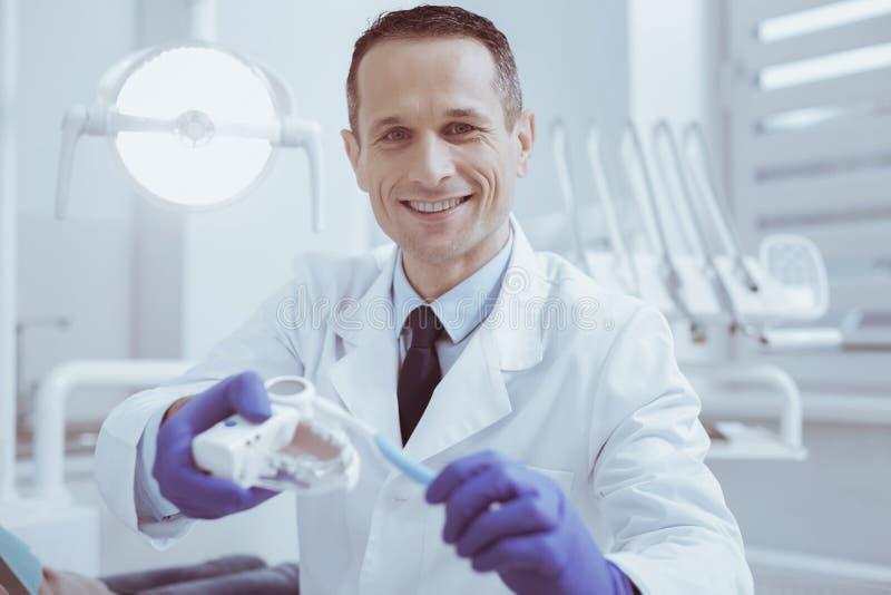 Modelo masculino alegre de la dentadura de la limpieza del dentista fotografía de archivo