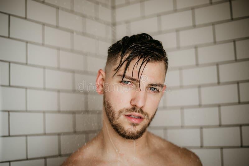 Modelo masculino atractivo joven Washing Hair en ducha mojada de la teja moderna de moda del subterráneo fotos de archivo