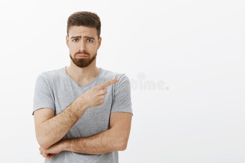 Modelo masculino barbudo encantador triste y lindo en la camiseta gris que frunce el ceño haciendo la cara melancólica con las ce imagen de archivo libre de regalías