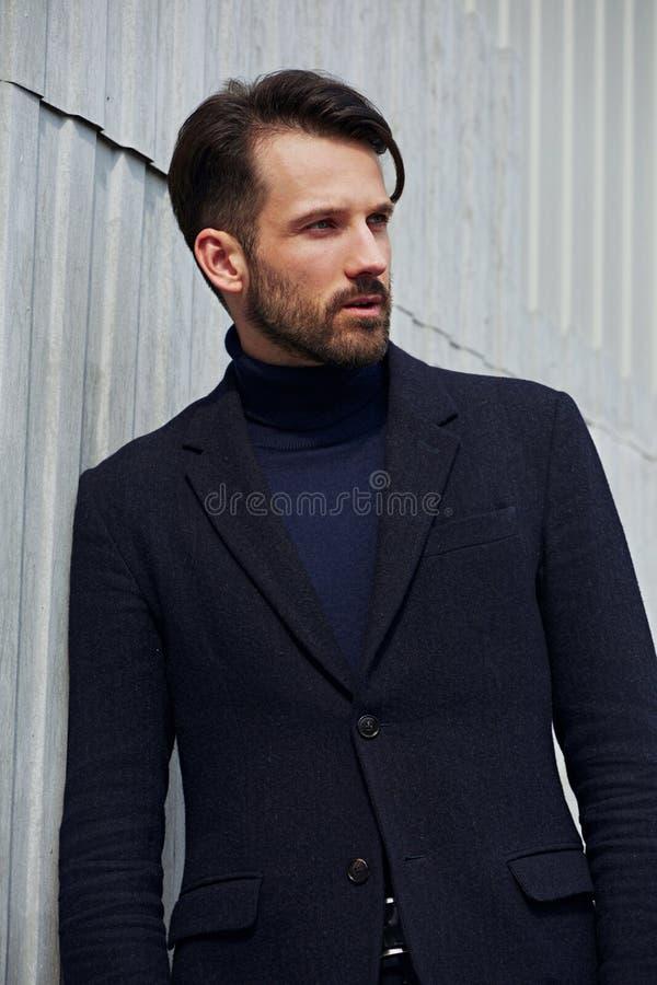 Modelo masculino consider?vel do neg?cio do estilo da barba da forma que levanta no casaco azul da roupa do estilo no fundo do ar imagem de stock royalty free