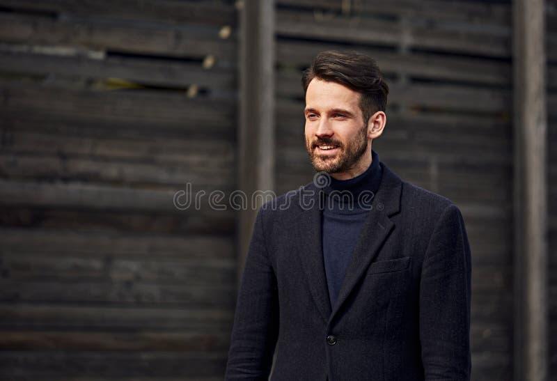 Modelo masculino consider?vel do neg?cio do estilo da barba da forma que levanta no casaco azul e na cal?as da roupa do estilo na foto de stock royalty free