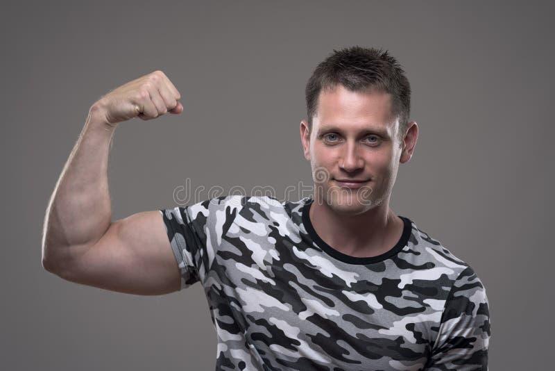 Modelo masculino da aptidão na camisa do exército que dobra o braço e que mostra os músculos do bíceps fotos de stock