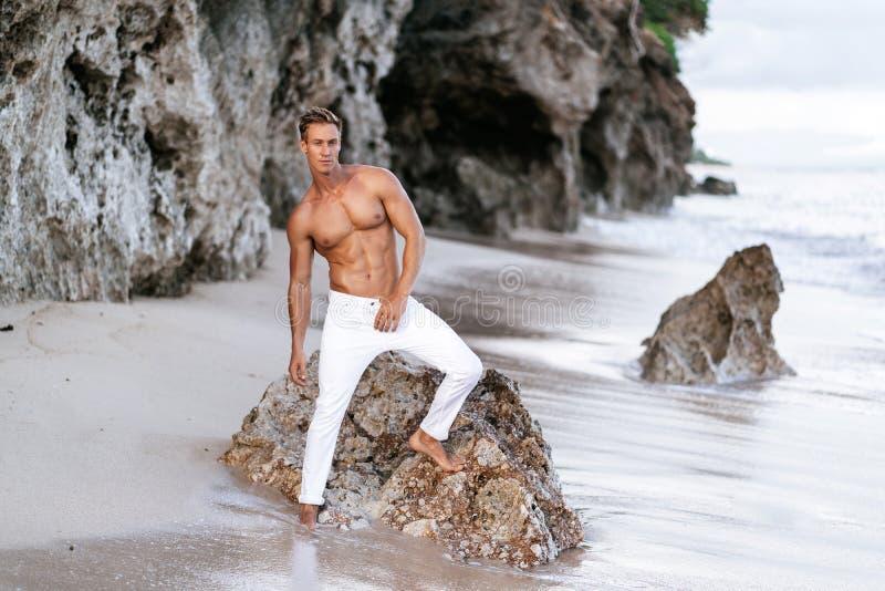 Modelo masculino da aptidão 'sexy' nas calças brancas e levantamento descamisado no Sandy Beach tropical fotografia de stock royalty free
