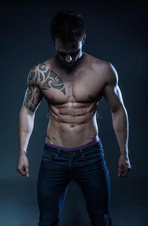 Modelo masculino de la aptitud con el tatuaje imagen de archivo