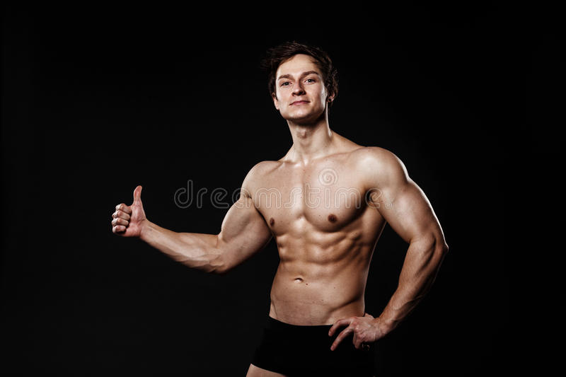Modelo masculino de la aptitud joven muscular y apta del culturista que muestra el th imagen de archivo libre de regalías
