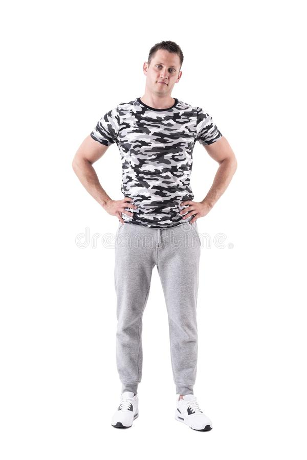 Modelo masculino de la aptitud joven relajada que presenta con las manos en caderas con la cabeza amontonada fotografía de archivo