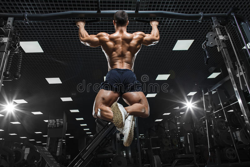 Modelo masculino de la aptitud muscular del atleta que levanta en barra horizontal imagenes de archivo