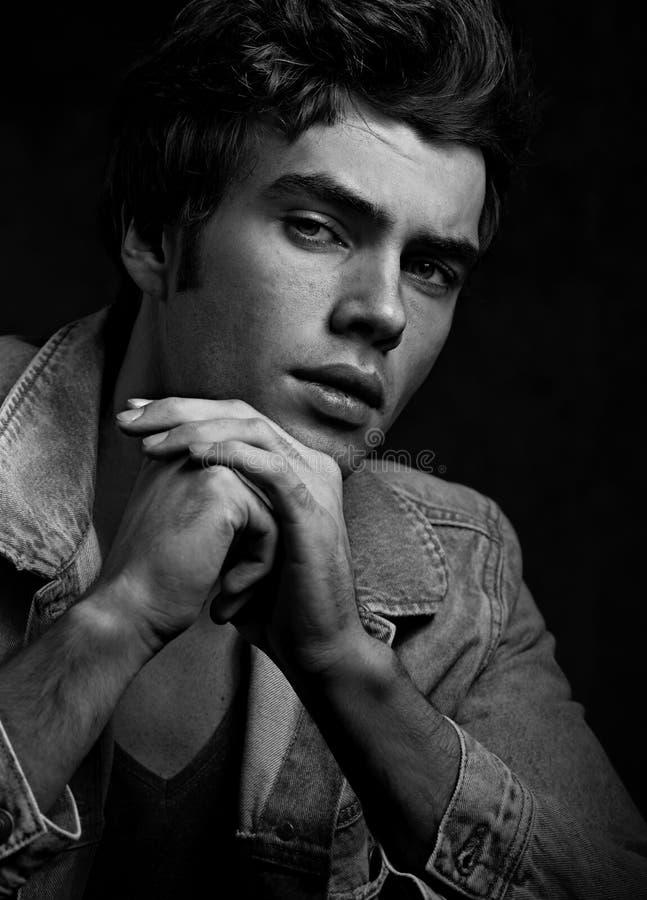 Modelo masculino de pensamento sério 'sexy' que levanta no casaco azul em s escuro fotografia de stock