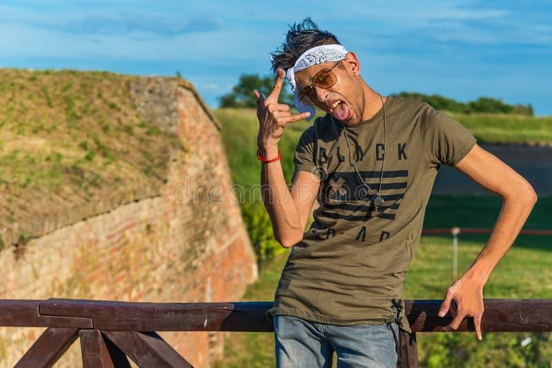 Modelo masculino do moderno extravagante com óculos de sol e um lenço branco em uma ponte de madeira O modelo mostra o dedo como  fotos de stock