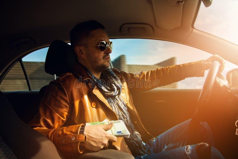 Modelo masculino elegante que sostiene un lor del dinero EUR y que conduce el coche imagen de archivo