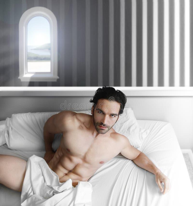 Modelo masculino en dormitorio imagen de archivo libre de regalías