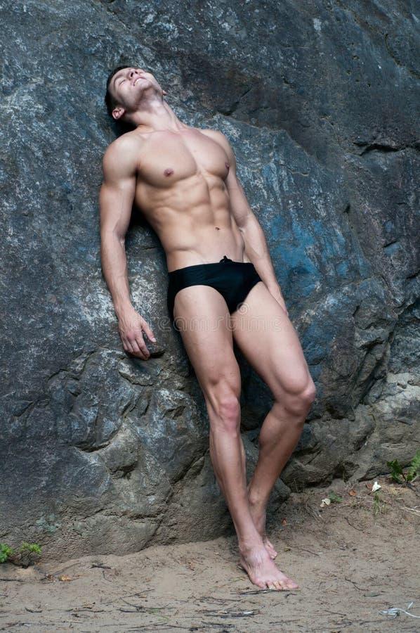 Modelo masculino en la roca imagenes de archivo