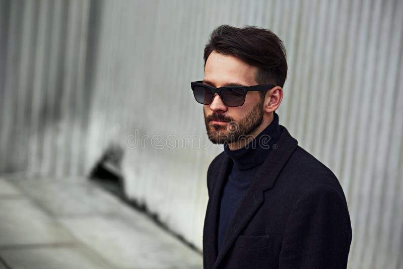 Modelo masculino hermoso del negocio del estilo de la barba de la moda en gafas de sol de la moda y capa azul con la mirada conce fotos de archivo