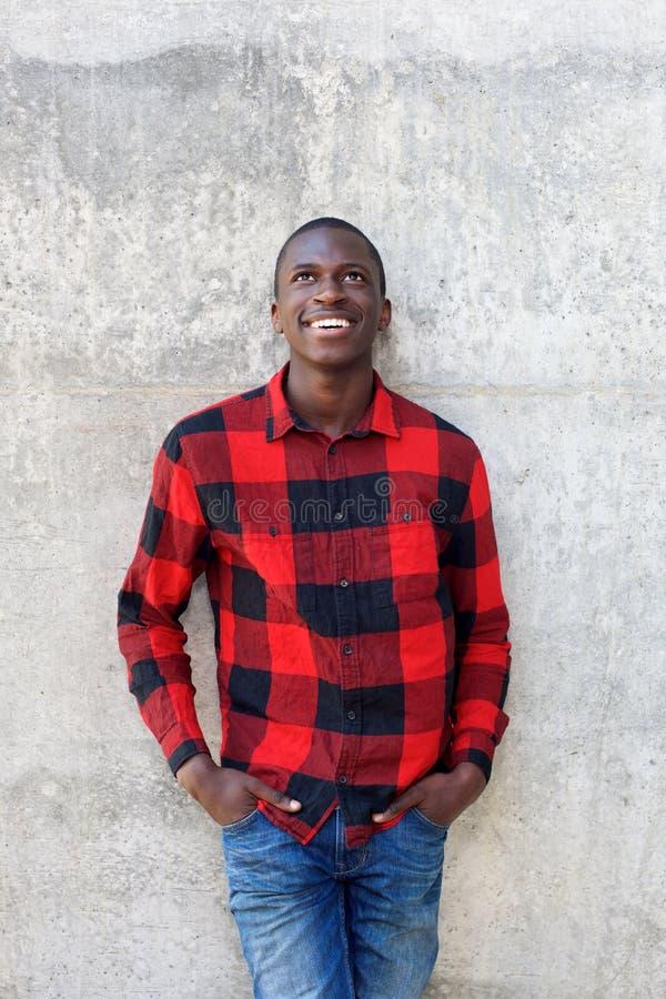Modelo masculino joven feliz que se inclina para emparedar fotos de archivo libres de regalías