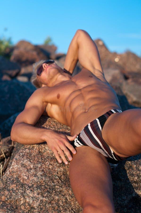 Modelo masculino nas rochas foto de stock