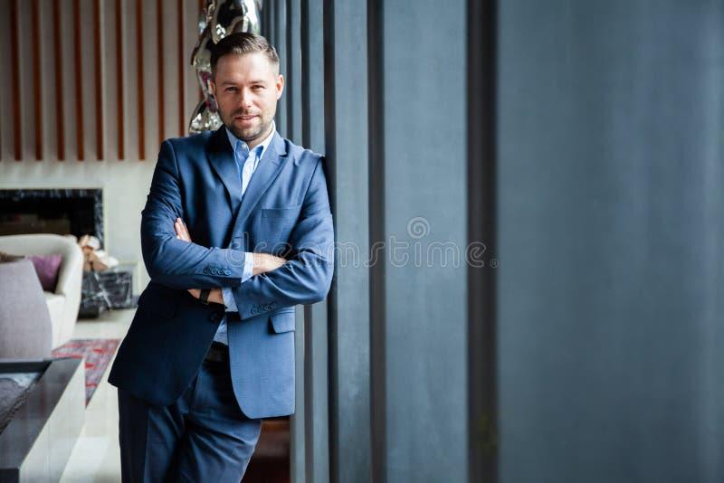 Modelo masculino no terno de negócio Os braços estando do homem de negócios novo seguro feliz cruzaram-se, sorrir, olhando a câme fotografia de stock