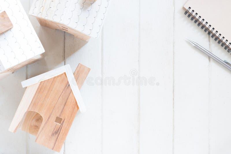 Modelo miniatura de la casa con el lápiz y el cuaderno imagen de archivo libre de regalías