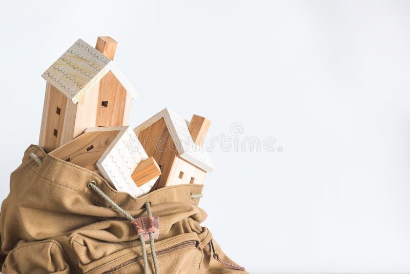 Modelo miniatura de la casa en la mochila marrón del color en el fondo blanco fotografía de archivo libre de regalías