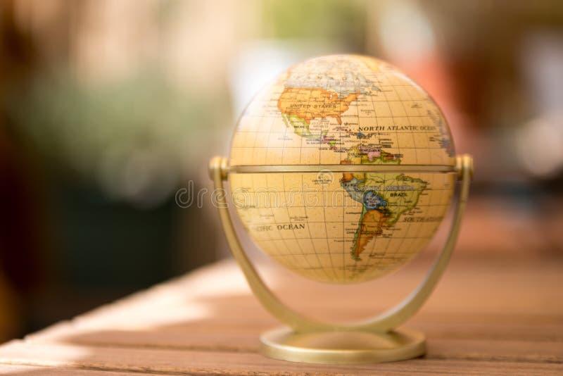 Modelo miniatura del globo en una tabla de madera rústica Símbolo para viajar imagen de archivo libre de regalías